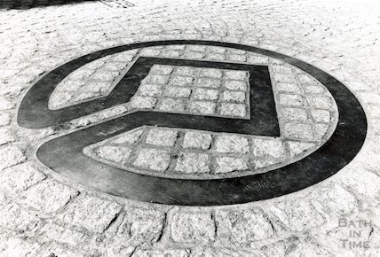 The bronze World Heritage symbol laid in the road at the end of Bath Street, 12 July 1988