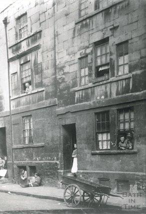 Faces in doorways and windows, Milk Street, c.1900