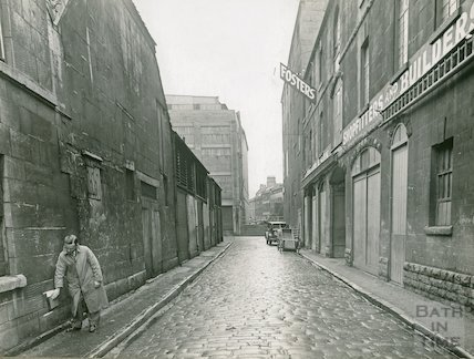 An inspector marks the high water mark from a recent flood, Back Street, Bath c.1930s