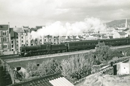 Westbound train pulling out of Bath Spa station and approaching the goods depot, c.1960s