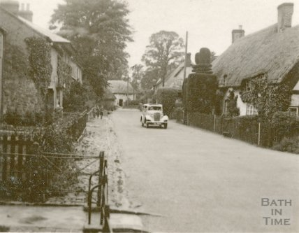 The photographer's car in an unidentified village with thatched cottages, c.1930s