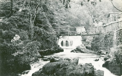 Unidentified rustic bridge over a river after a waterfall, c.1910s