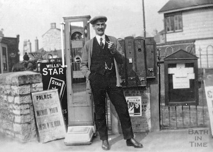 A gentleman in front of stamp machines and the Radstock West signal box, c.1900s