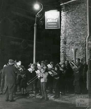 People playing brass instruments besides the Kings Head Pub, c.1970