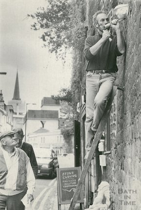 A stone mason carving a gargoyled head into a wall on Walcot Street, Bath, 18th May 1993