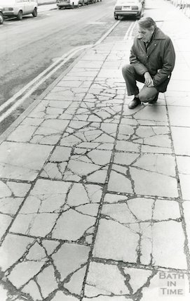 Man looking at pavement cracks left by lorries on Monmouth Street, Bath, 6th March 1987
