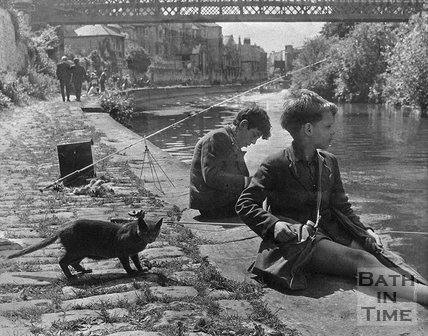 Two boys and a cat fishing on the riverbank below Claverton Street, c.1960s