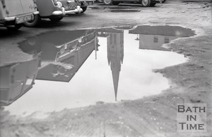 Reflection of St John's catholic church in a puddle, c.1970