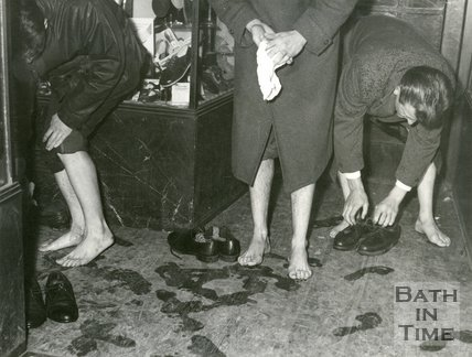 Taking off shoes and socks to cope with the Bath Floods, 1960
