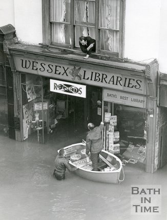 A rowing boat delivers emergency supplies to someone stranded by the flood in Bath, 1960