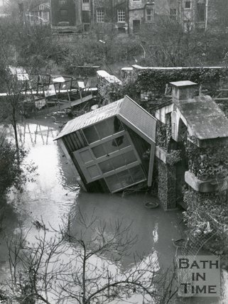 A summer house lies on its side next to Delia's Grotto, North Parade, Bath, 1960