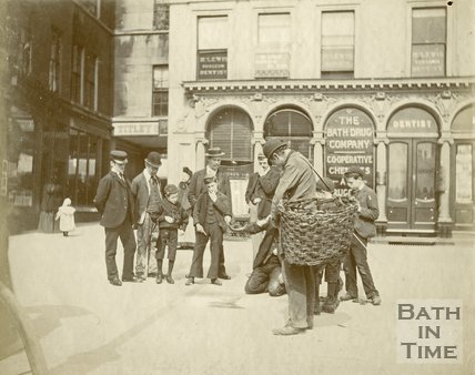 A gathering in Abbey Church Yard outside the Bath Drug Company chemist shop, Bath c.1895