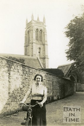 A lady with her bicycle outside the church at Bathford, near Bath, c.1920s