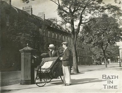 A man in a bath chair posts a letter in the tree-line Great Pulteney Street, c.1930s