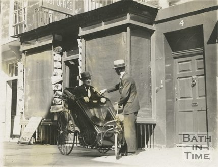 A man in a bath chair outside the Post Office in Margarets Buildings, Bath, c.1930s