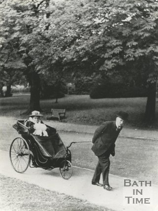 A gentleman pulls a lady in a bath chair in Royal Victoria Park, c.1910