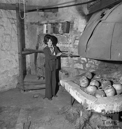 Jane Perry-Smith beside an old forge, soon to be her new boutique, 11 Beaufort Square, 5 January 1973