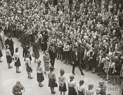 Flanked by a female guard of honour, the Princess Elizabeth walks through the masses, Bath 1945