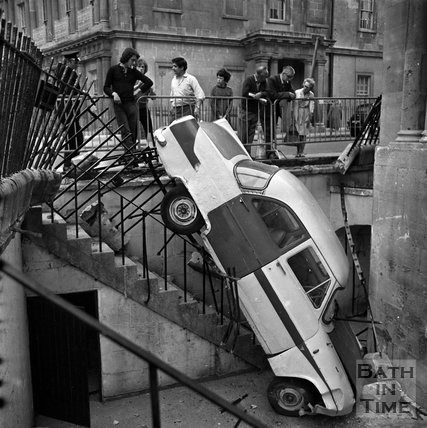 A car that has crashed through the railings at the Circus, Bath, c.1960s
