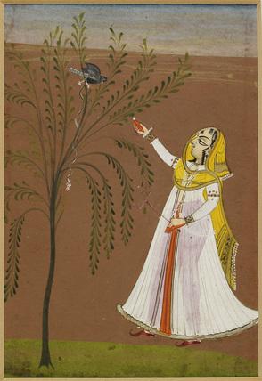 Lady feeding a bird in a tree