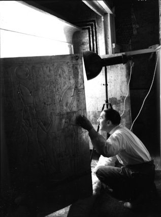 Howard Carter looking through the doors of the second shrine
